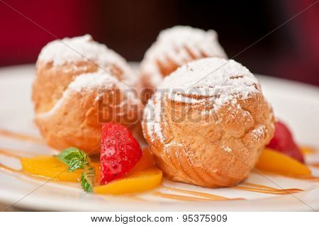 profiteroles from cream and condensed milk decorated with strawberry and peach