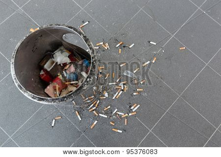 Dirty cigarette butts and ashtray in an airport