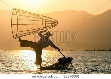 Acrobat Burmese fisher in Inle lake,standing on the canoe and holding fishing trap