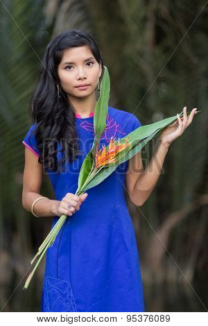Young pretty Vietnamese woman in blue Ao Dai dress holding orange flowers with big leaves, looking the camera.