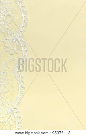 Yellow Delicate satin background with lace border. Vertical image.