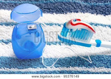 Dental floss and a blue toothbrush on a towel