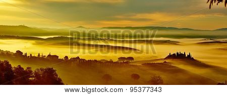 Scenic Tuscany landscape panorama with rolling hills and valleys in golden morning light.