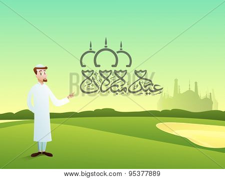 Religious Muslim man pointing towards Arabic calligraphy of text Eid Mubarak on mosque silhouetted nature background for Islamic festival celebration.
