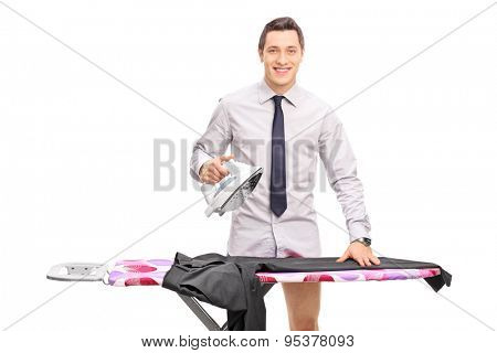 Young man with a gray shirt and tie ironing his pants on an ironing board and looking at the camera isolated on white background