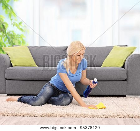 Young blond woman cleaning a carpet in front of a gray sofa with a rag at home shot with tilt and shift lens