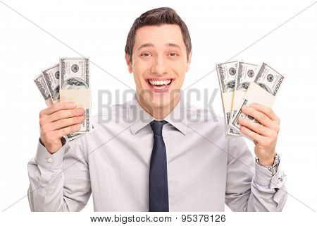 Joyful young man holding six stacks of money and looking at the camera isolated on white background