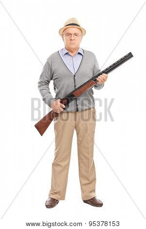 Full length portrait of a serious senior gentleman holding a shotgun and looking at the camera isolated on white background