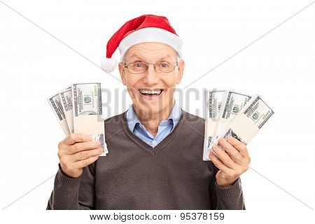 Senior with Santa hat holding six stacks of money and looking at the camera isolated on white background