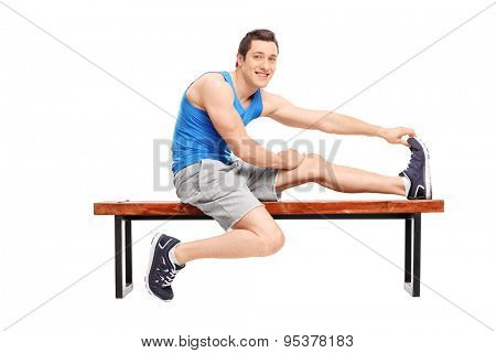 Young male athlete stretching his leg seated on a wooden bench and looking at the camera isolated on white background