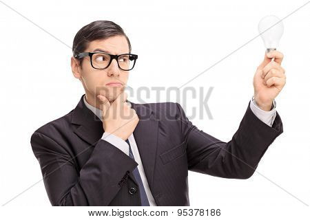 Young businessman looking at a light bulb and thinking isolated on white background