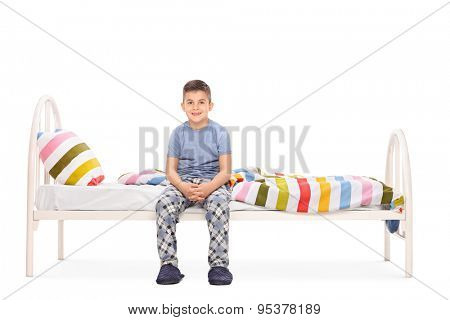 Boy in blue pajamas sitting on a bed and looking at the camera isolated on white background