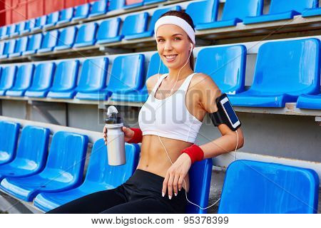 Happy girl in activewear looking at camera at stadium