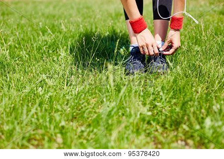 Hands of sporty woman tying shoelaces of her sneakers while standing on green lawn