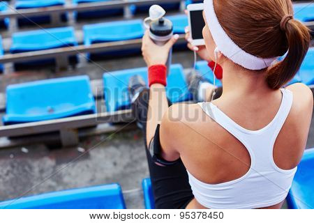 Back of young woman in activewear sitting at stadium