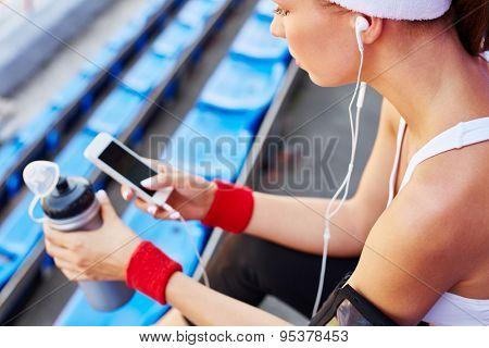 Modern girl in activewear using iphone at stadium