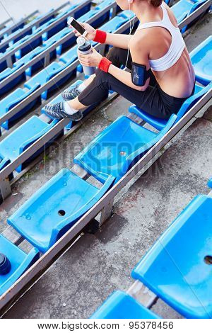 Young female in activewear sitting at stadium at leisure