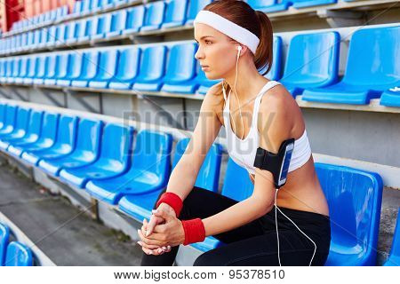 Girl with earphones in activewear spending leisure at stadium