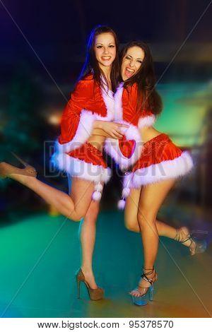 Two Santa-girls on dance floor in the nightclub