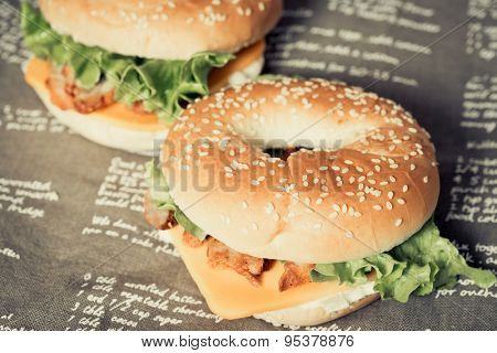 Bagel with fresh cheese and fresh lettuce on napkin