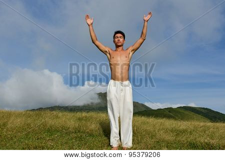 Full yong muscular man stretching his hands on mountain
