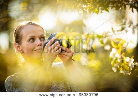 Pretty female amateur photographer taking photos outdoors, doing what she loves to do