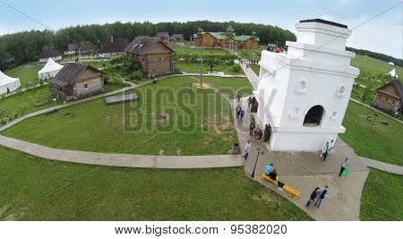 RUSSIA, BOROVSK - JUN 13, 2014: Aerial view of people walk near monument of Russian native stove on territory of cultural complex Etnomir at summer day. Photo with noise from action camera