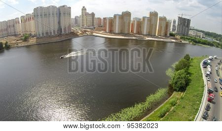 RUSSIA, KRASNOGORSK - JUN 6, 2014: Riverscape and tall dwelling houses on shore at summer day. Aerial view. Photo with noise from action camera