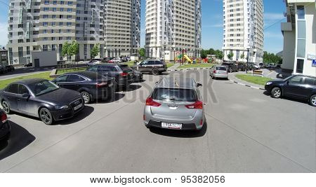RUSSIA, MOSCOW - JUN 24, 2014: Aerial view of car rides by yard with playground near residential complex on Elk Island at sunny day. Photo with noise from action camera