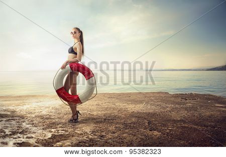 Fashionable woman holding a life buoy