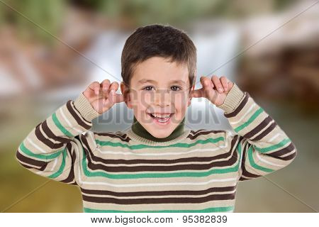 Nice boy covering the ears with unfocused background