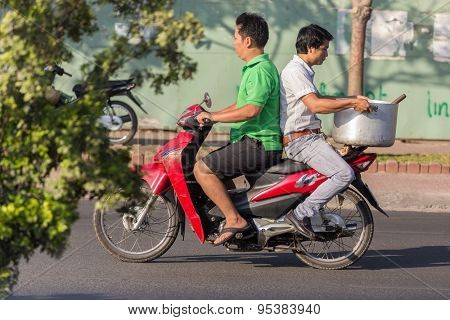 HO CHI MINH CITY ( SAIGON ), VIETNAM, FEBRUARY 21, 2015 : A man is riding a motorbike , his friend is sitting at the opposite side holding a large kitchen recipient, Ho Chi Minh City, Vietnam