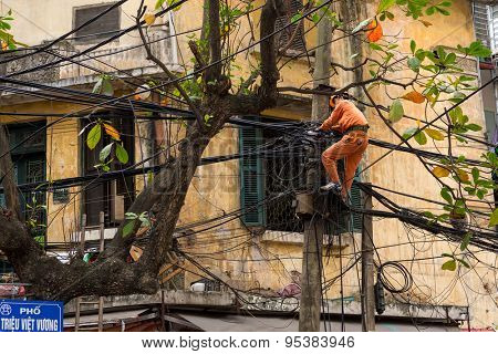 HANOI, VIETNAM, DECEMBER 16, 2014 : A technician is repairing or checking the messy electrical network in the city of Hanoi, Vietnam