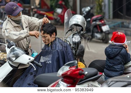HANOI, VIETNAM, DECEMBER 15, 2014 : A nomad hairdresser is working outside in the city , his customer is sitting on his motorbike in Hanoi, Vietnam.