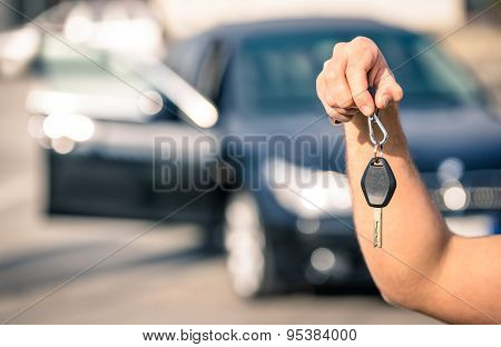 Man's Hand Holding Modern Car Keys Ready For Rental - Concept Of Transportation With Automobile