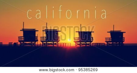 the word California and some lifeguard towers in Venice Beach, California, United States, at sunset