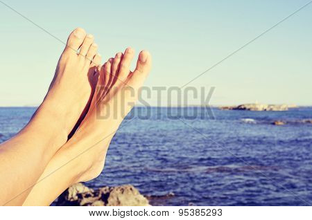 closeup of the bare feet of a young caucasian man relaxing on the sea in Ibiza Island, Spain, with Formentera Island in the background