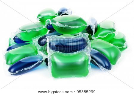 closeup of a pile of liquid laundry detergent sachets on a white background