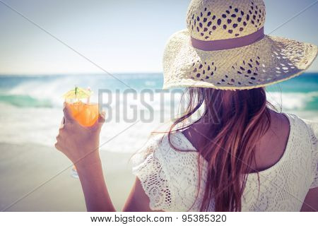 Brunette wearing straw hat and holding a cocktail at the beach