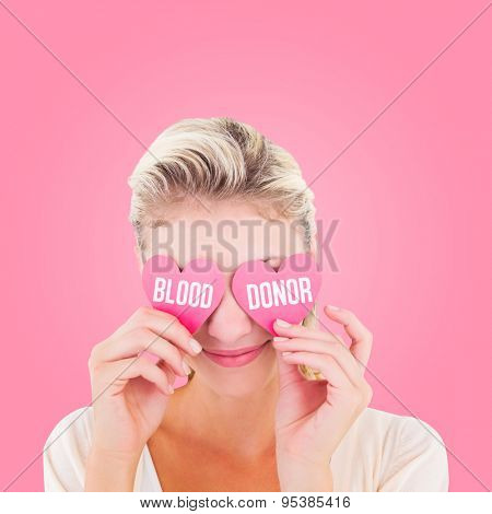 Attractive young blonde holding hearts over eyes against pink