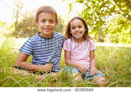 Siblings sitting outdoors on a sunny day, looking to camera