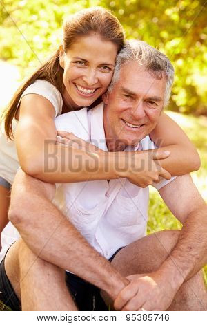 Senior man embraced by his adult daughter, outdoors