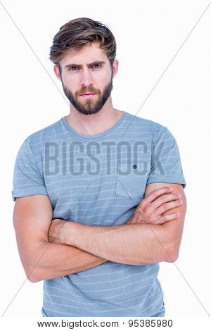 Unhappy handsome man looking at camera with arms crossed on white background