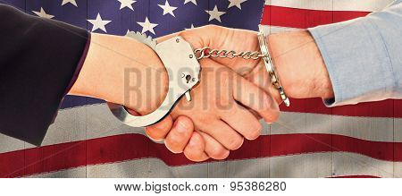 Business people in handcuffs shaking hands against pale grey wooden planks