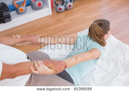 Woman stretching her arm with trainer in fitness studio