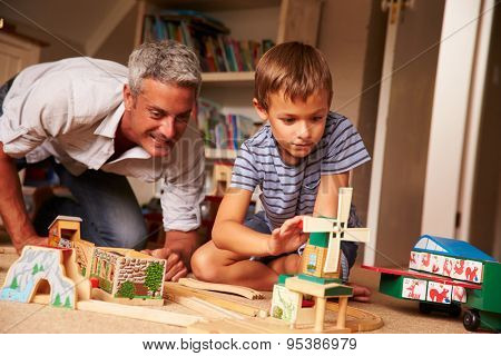 Father playing with son and toys on the floor in a playroom