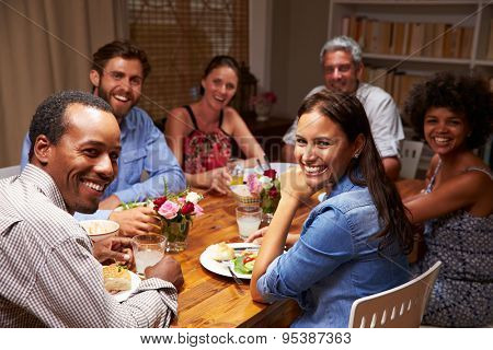 Friends at an evening dinner party, looking at camera