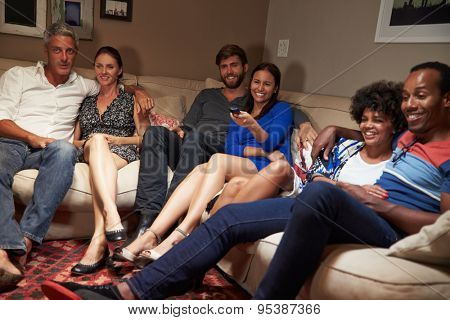 Group of adult friends watching television together