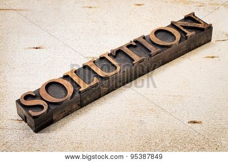solution word in vintage letterpress wood type against white painted rustic barn wood