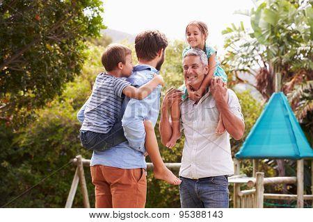 Two men piggybacking kids in a garden